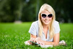 Female student reading book on the green grass Stock Photo