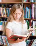 Female student reading book in library Royalty Free Stock Photos
