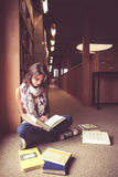 Female student reading a book in the library aisle Royalty Free Stock Photos