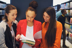 Female student reading a book in a library. Multiethnic young students reading a book in library. Standing in public library sharing reference book for their Royalty Free Stock Photo