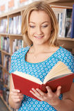 Female Student Reading Book In Library Stock Photo