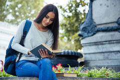 Female student reading book outdoors Stock Photo