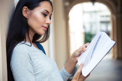 Female student reading book outdoors Stock Photography