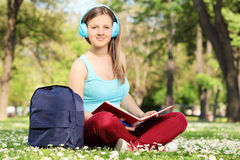 Female student reading a book in park. And looking at the camera Royalty Free Stock Image
