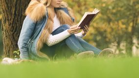 Female student reading book in park, pleasant pastime in fresh air, relaxation. Stock footage stock video