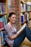 Female student reading a book sitting on the floor. In a bookstore Royalty Free Stock Photography