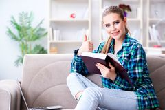 The female student reading the book  sitting on the sofa. Female student reading the book  sitting on the sofa Royalty Free Stock Photo