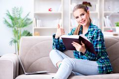 The female student reading the book  sitting on the sofa. Female student reading the book  sitting on the sofa Royalty Free Stock Images
