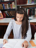 Female Student Reading Book At Table In Library Stock Photography