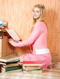 Female student reading books. Pretty female student reading books on sofa at home Royalty Free Stock Photo