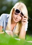 Female student reading interesting book on the grass Stock Images