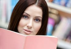 Female student reads the book at the library Royalty Free Stock Photo