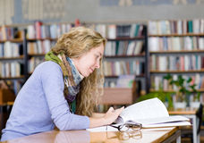 Female student reads the book in library Royalty Free Stock Image