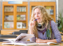 Female student reads the book in library Stock Image