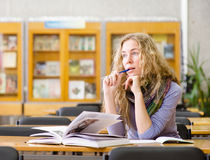 Female student reads the book in library. looking away Royalty Free Stock Photo