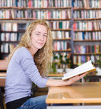 Female student reads the book in library. Royalty Free Stock Photography
