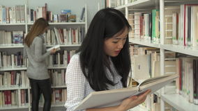 Female student reads book at the library. Pretty asian female student reading book at the library. Attractive brunette woman smiling for the camera with textbook stock video footage