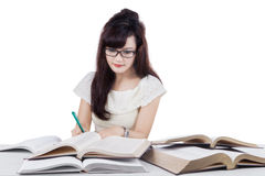 Female student reads book and writing. Pretty female college student reading books while writing on the book, isolated on white background Royalty Free Stock Photography