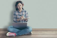 Female student relaxed sitting on a wooden floor at home and watching training online course and listening it with headphones. From compute laptop. online stock image