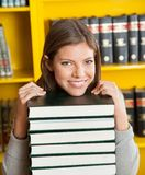 Female Student Resting Chin On Piled Books In. Portrait of confident female student resting chin on piled books in college library Royalty Free Stock Images