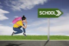 Female student running toward to school royalty free stock photos