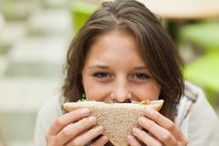 Female student with sandwich in the cafeteria Royalty Free Stock Photos