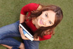 Female student seated on grass and holding a couple of books Stock Image