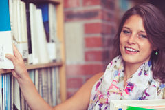 Female student selecting book from the shelf in library Stock Photography