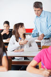 Female Student Showing Paper To Teacher At Desk Royalty Free Stock Photography