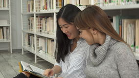 Female student shows her classmate something in the book stock video