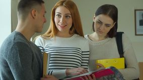 Female student shows her exercise book to her male classmate royalty free stock image