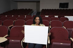 Female Student With Sign Board In Classroom Royalty Free Stock Images