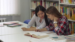 Female student sits down near her classmate at the library stock video footage
