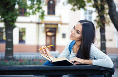 Female student sitting on the bench with book Stock Image