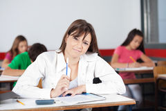 Female Student Sitting In Classroom. Portrait of female student sitting at desk in classroom Royalty Free Stock Photography