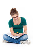 Female student sitting crossed legs, writing Stock Images