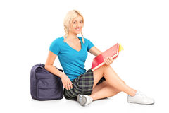 Female student sitting on floor Stock Images
