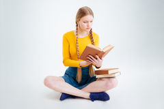 Female student sitting on the floor and reading book Stock Image