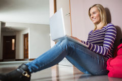 Female student sitting on flooring using laptop Stock Photography