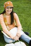 Female Student Sitting On Grass Stock Photography