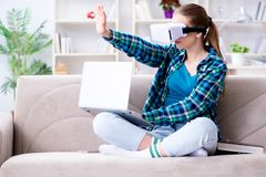 The female student sitting on the sofa with virtual glasses. Female student sitting on the sofa with virtual glasses Stock Image