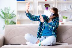 The female student sitting on the sofa with virtual glasses. Female student sitting on the sofa with virtual glasses Royalty Free Stock Photos