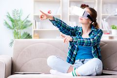 The female student sitting on the sofa with virtual glasses. Female student sitting on the sofa with virtual glasses Stock Images