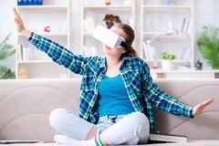The female student sitting on the sofa with virtual glasses. Female student sitting on the sofa with virtual glasses Royalty Free Stock Images