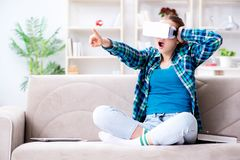 The female student sitting on the sofa with virtual glasses. Female student sitting on the sofa with virtual glasses Royalty Free Stock Photo