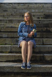 Female student sitting on stairs with book Royalty Free Stock Images