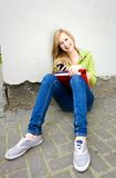 Female student sitting by the wall. Teenage girl sitting by the wall Stock Images