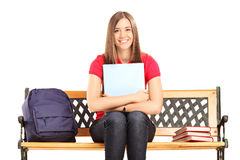 Female student sitting on a wooden bench and holding a notebook Stock Photography