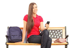 Female student sitting on a wooden bench and typing a sms Royalty Free Stock Images