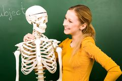Female student with skeleton. Standing in front of chalkboard stock images